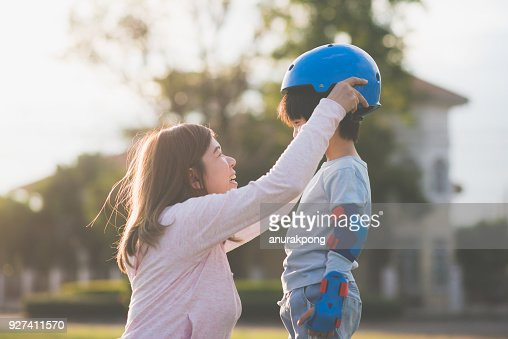 Asian mother helping her son wears blue helmet on enjoying time together in the park : Stock Photo