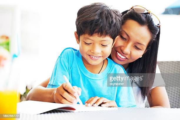 Asian mother helping her son with his homework