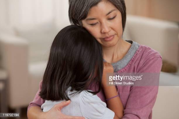 Asian mother hugging daughter