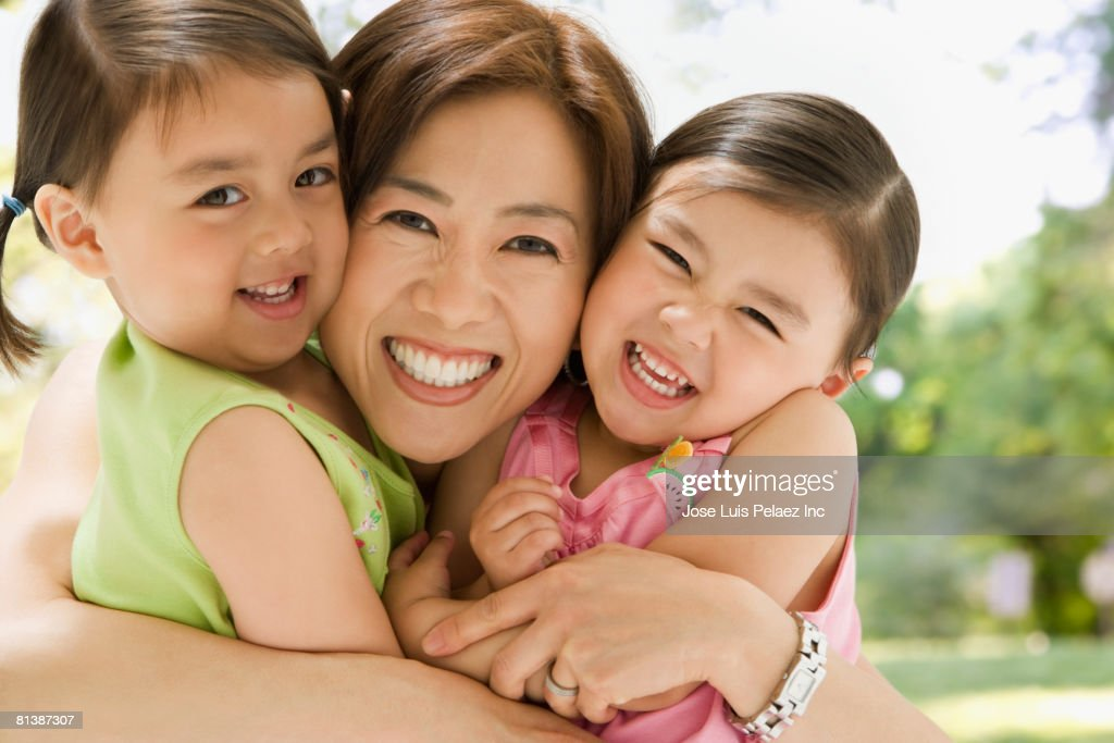 Asian mother hugging daughters : Stock Photo