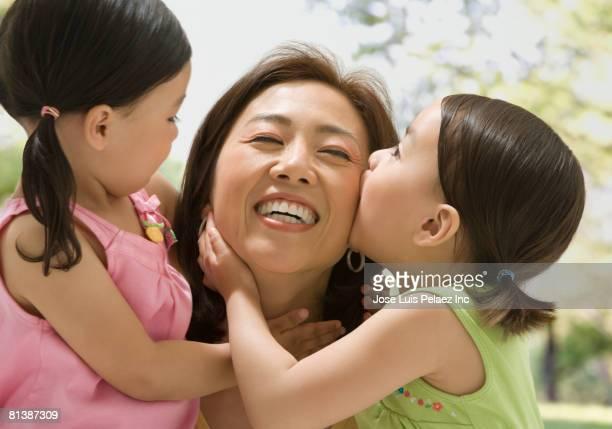 Asian mother hugging daughters
