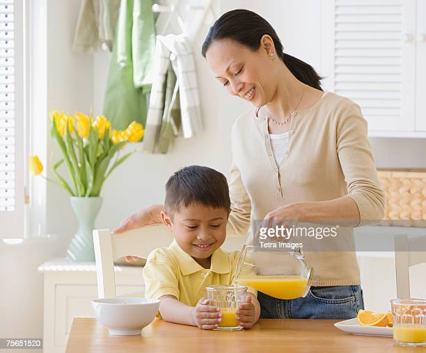 Asian mother pouring juice for son