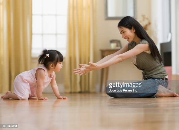 Asian mother reaching out to baby daughter