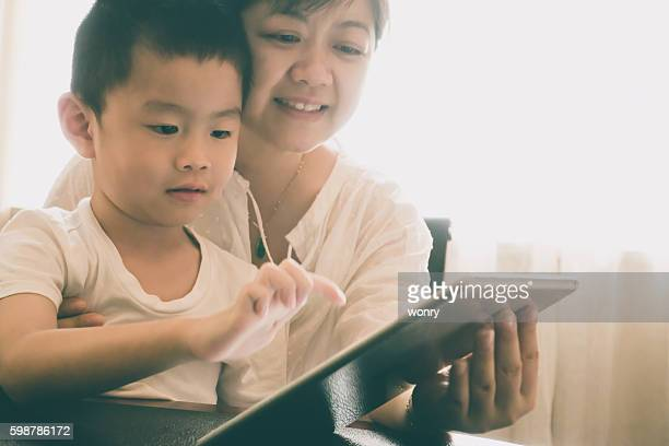 Asian mother teach son with digital tablet indoors