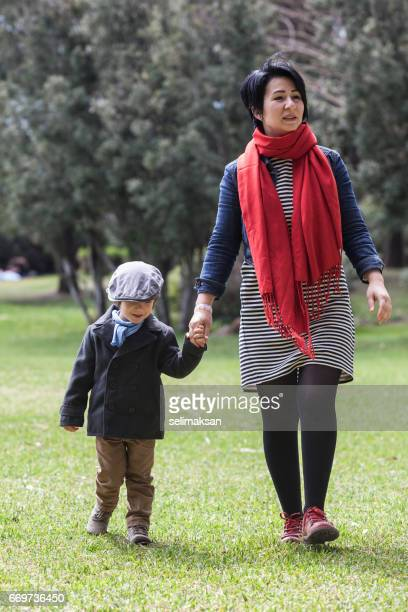 Asian Mother Walking In Public Park With Her Son