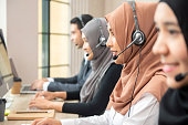 Asian muslim women wearing microphone headsets working as customer service operator team in call center office