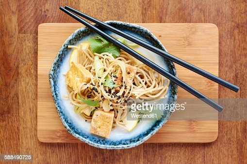 Asian noodle salad with soba noodles, tofu, green onions, yellow zucchini and coriander, garnished with black sesame seeds