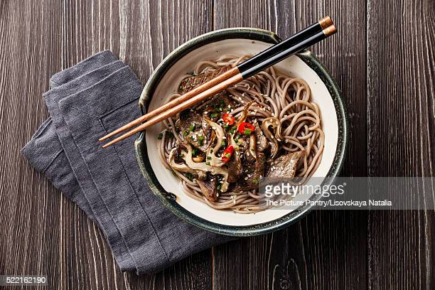 Asian noodles Yakisoba with beef and oyster mushrooms in bowl on