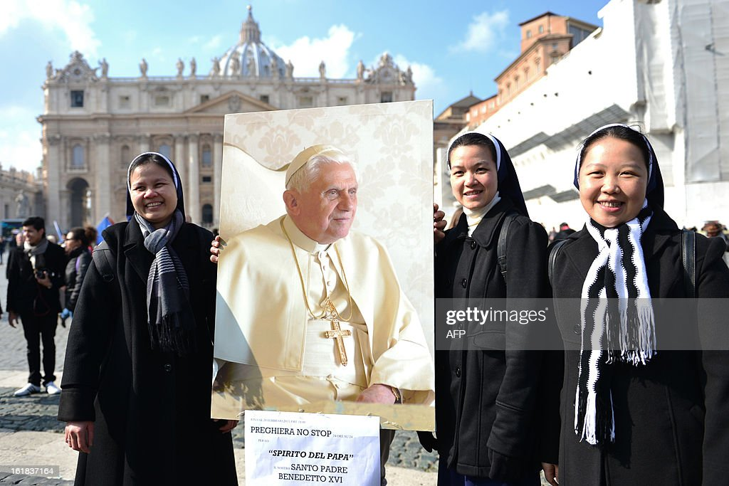 Asian nuns hold a portrait of Pope Benedict XVI on St Peter's square after the Angelus prayer led by Pope Benedict XVI from the window of his appartments on February 17, 2013 at the Vatican. The Vatican the day before said it could speed up the election of a new pope as lobbying for Benedict XVI's job intensified amid speculation over who had the best chance to succeed him.