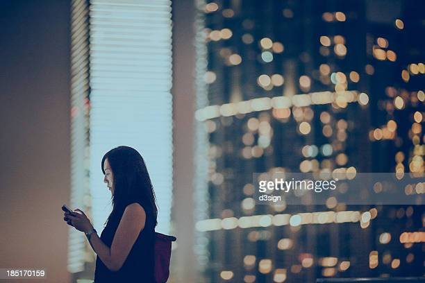 Asian office lady using her smartphone in city