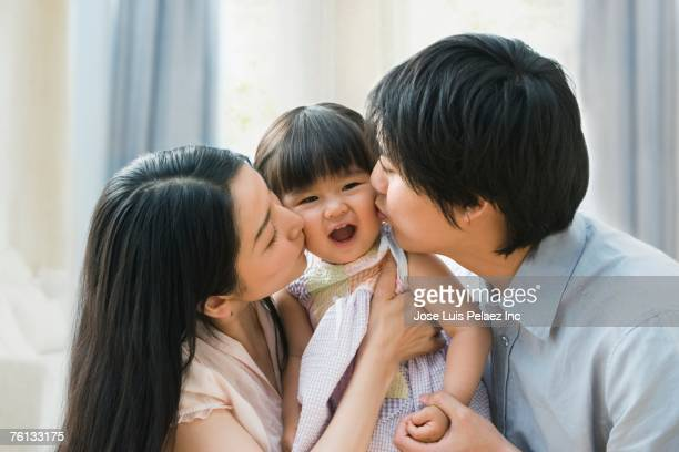 Asian parents kissing baby daughter's cheeks
