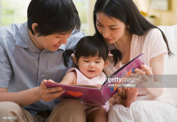 Asian parents reading to baby daughter