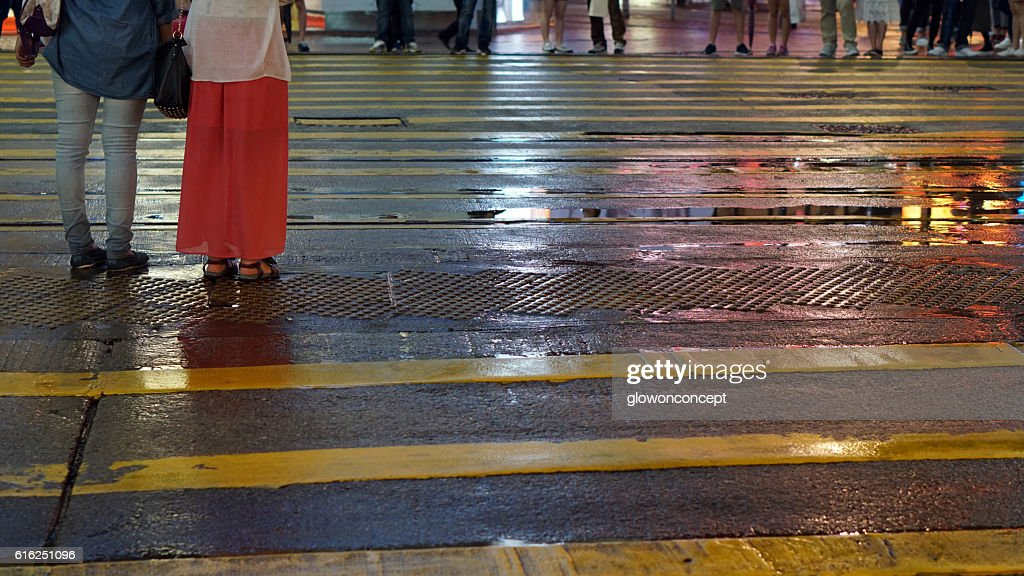 Asian people cross wet street with neon light reflection : Foto de stock