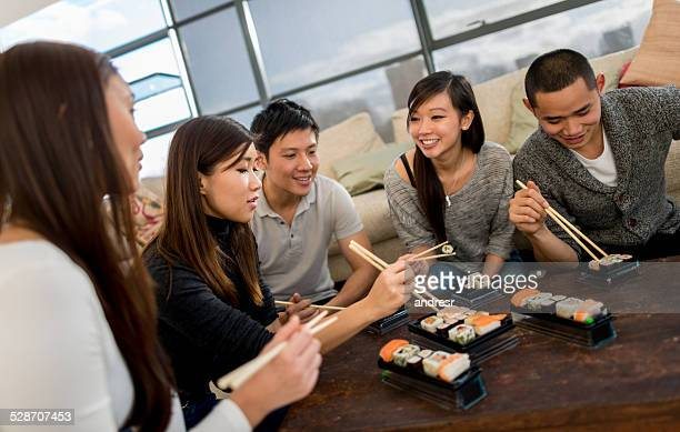 の寿司を食べるアジア人