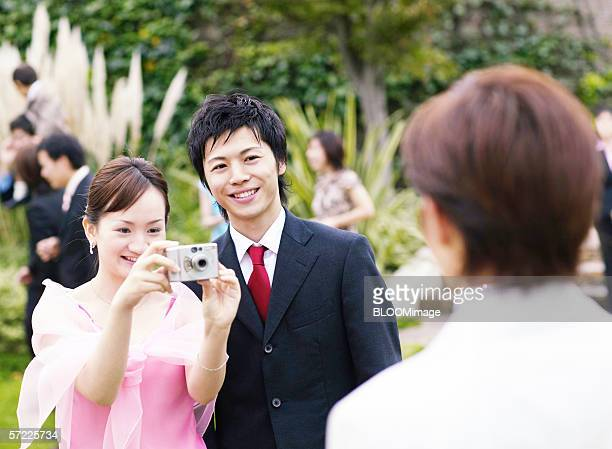 Asian people taking bride and bridegroom' photographs