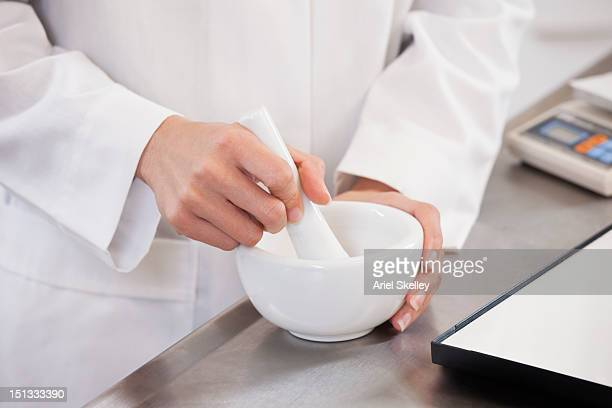 Asian pharmacist mixing medication