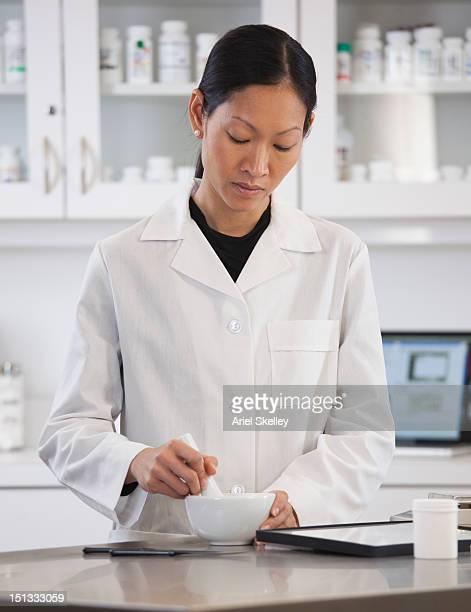 Asian pharmacist preparing medication