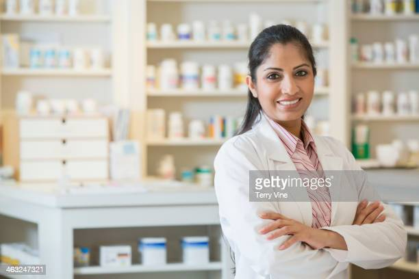 Asian pharmacist smiling at counter
