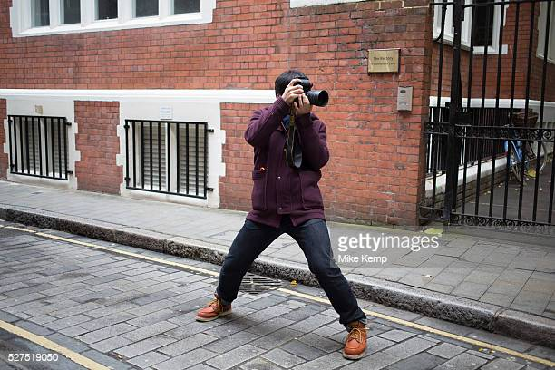 Asian photographer photographing a Chinese couple for their wedding pictures London UK This is a common sight as couples from Asia have their...