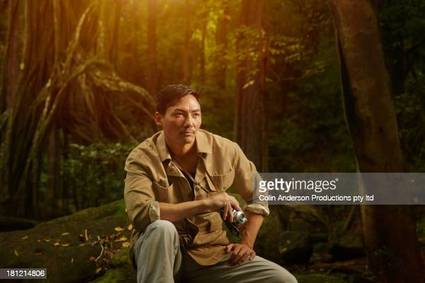 Asian photographer sitting in jungle