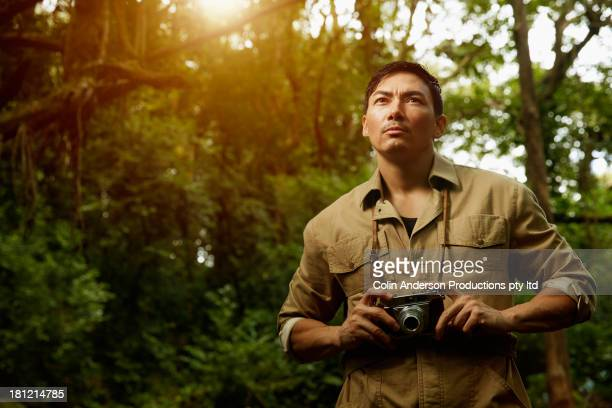 Asian photographer standing in jungle