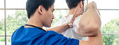 Asian physical therapist stretching athlete male patient shoulder and back in clinic, panoramic banner