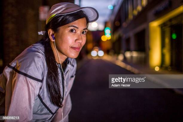 Asian runner resting on city street at night