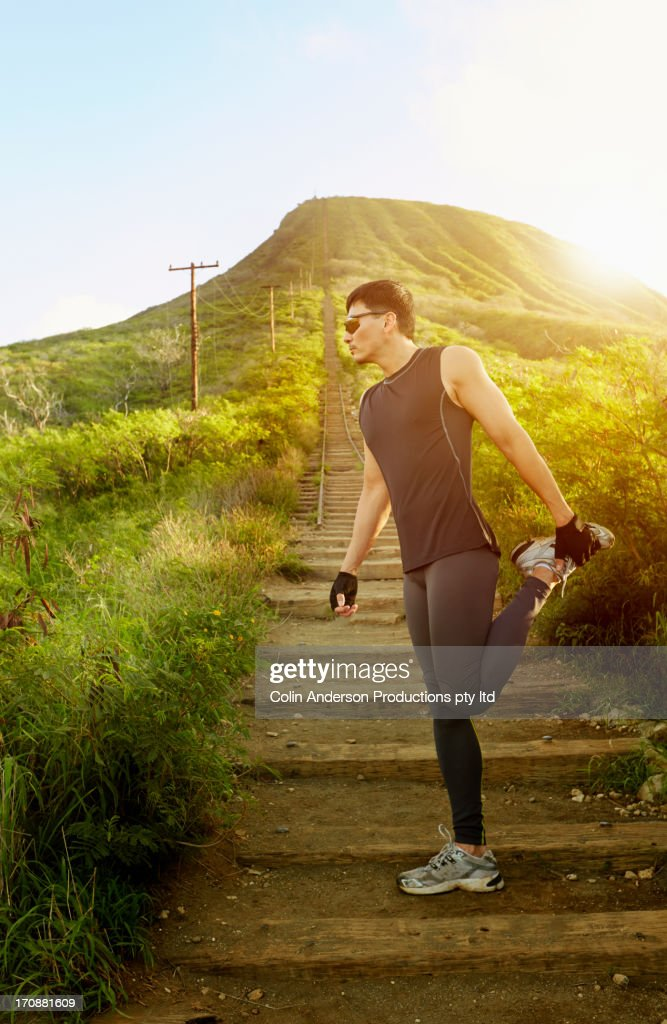 Asian runner stretching on abandoned train tracks