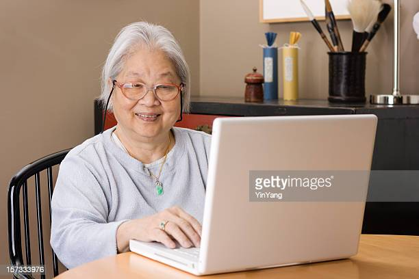 Asian Senior Adult Woman Using Laptop Computer, Happy and Smiling