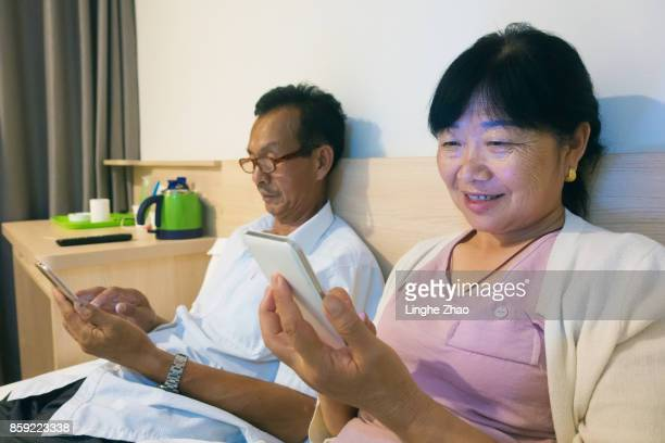 Asian senior couple using mobile phone on bed