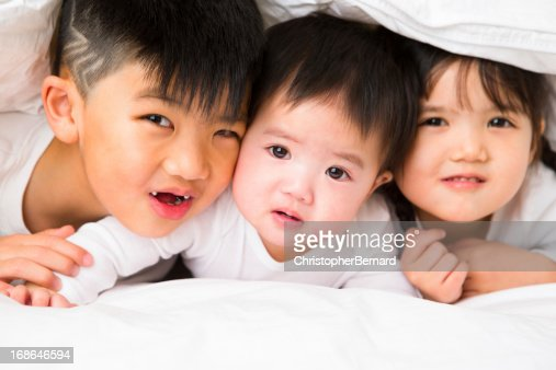 Asian sibling portrait on bed