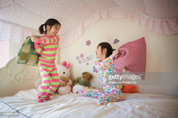 Asian sisters having pillow fight in bed