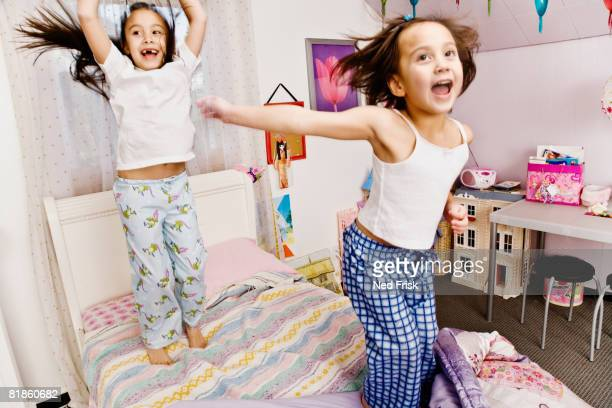 Asian sisters jumping on bed
