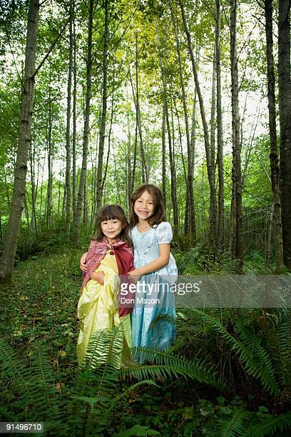 Asian sisters wearing costumes in woods