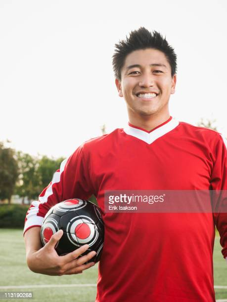 Asian soccer player holding ball on soccer field