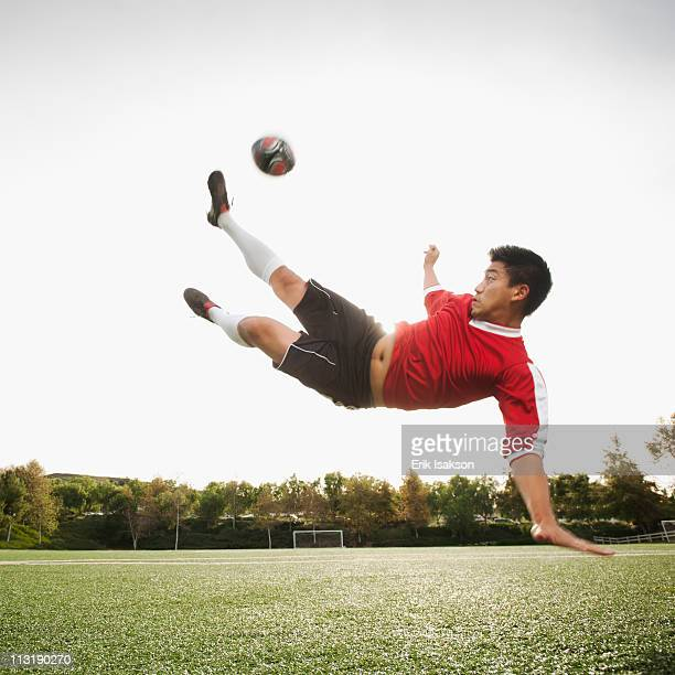 Asian soccer player in mid-air kicking soccer ball