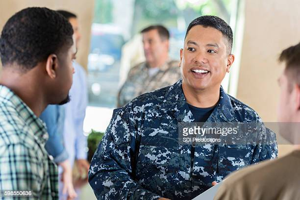 Asian soldier talking to young man at military recruitment event