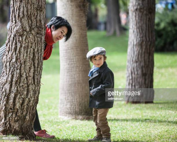 Asian Son And Mother Playing In Green Public Park
