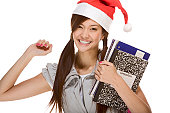 Asian schoolgirl wearing red Santa Claus hat with backpack holding Composition book, notebooks and pen