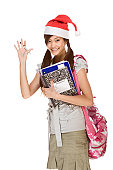 Asian school girl wearing red Santa Claus hat with backpack holding Composition book, notebooks and pen waives her hand making greeting gesture