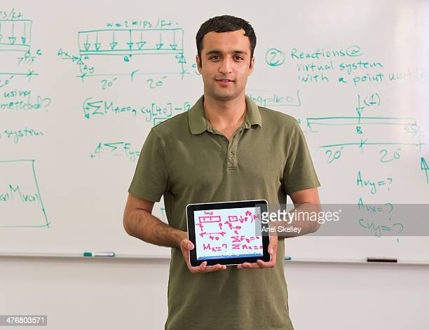 Asian student writing formula on digital tablet