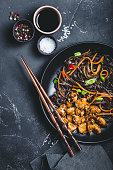 Asian soba noodles, chicken, vegetables, rustic concrete dark background. Soba noodles, teriyaki sauce chicken, vegetables, sesame, chopsticks. Asian style dinner. Chinese/Japanese noodles. Top view