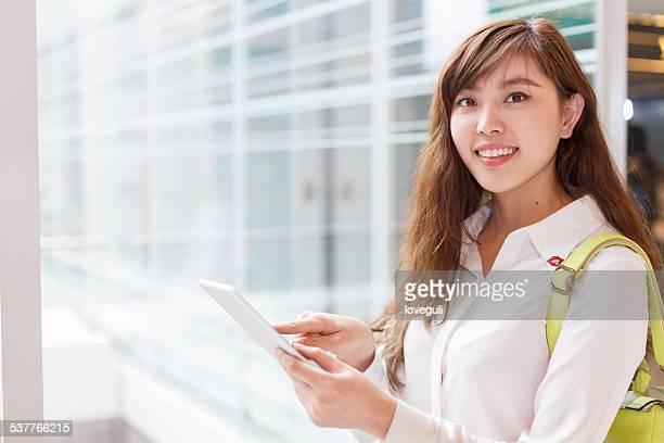 asian successful businesswoman using digital tablet at office corridor
