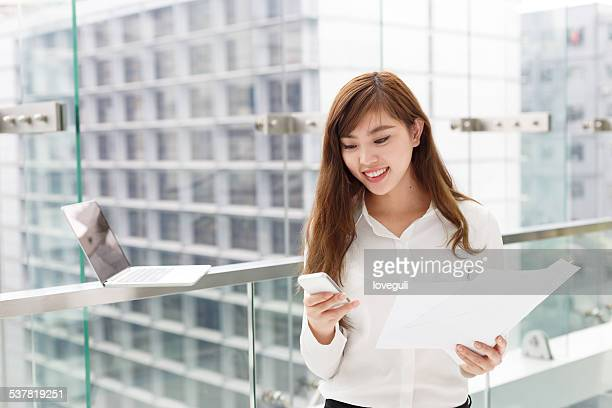 asian successful businesswoman using smart phone at office corridor