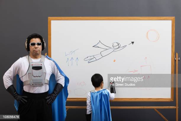 Asian superhero family looking at whiteboard