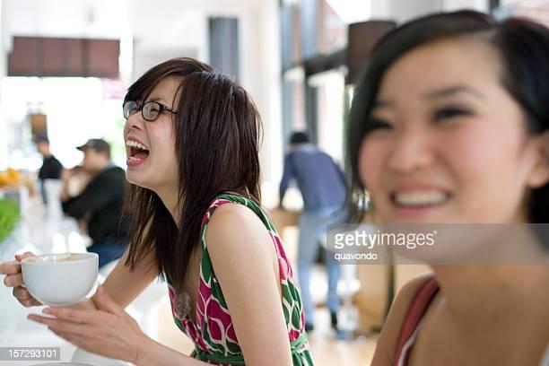 Asiatische Teenager-Freundinnen Lachen im Coffee Shop