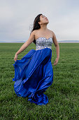 Asian teenage girl wearing gown in rural field