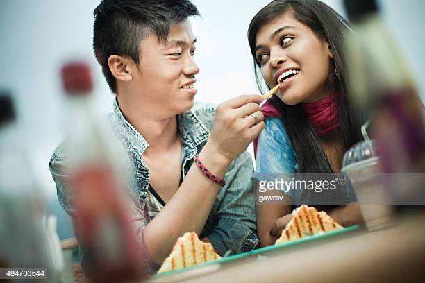 Asian teenage lovers of different ethnicity enjoying food at restaurant.