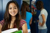 Asian teenaged girl in front of school lockers