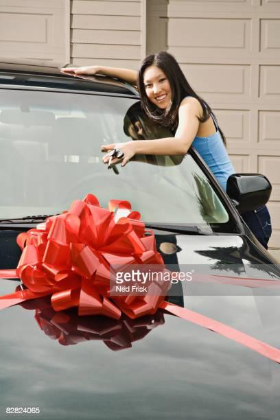 Asian teenager adoring new car